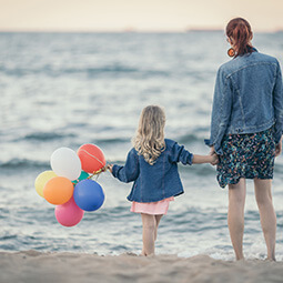 mum daughter beach balloons looking at the sea holding hands summer poland Baltic travel UGC content